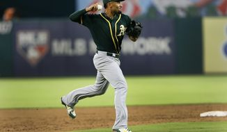 Oakland Athletics shortstop Marcus Semien throws to first during the sixth inning of a baseball game against the Texas Rangers, Tuesday July 24, 2018, in Arlington, Texas. (AP Photo/Roger Steinman)
