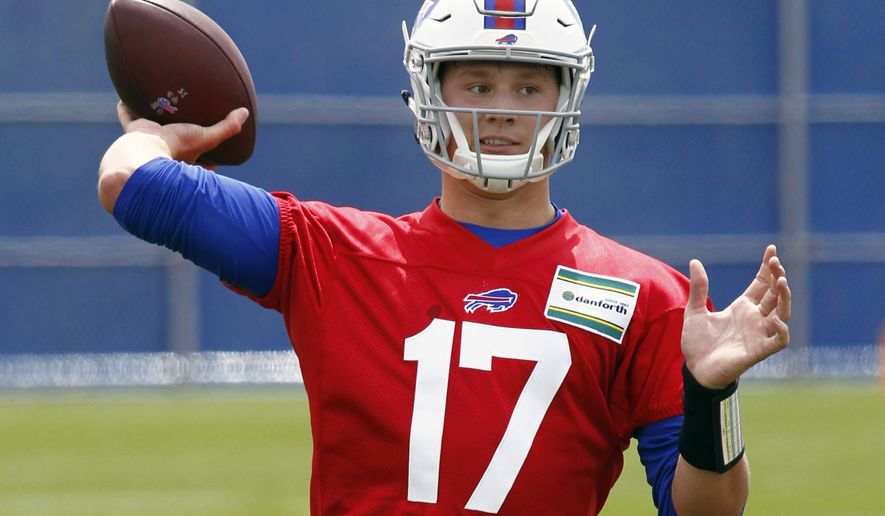 FILE - In this May 11, 2018, file photo, Buffalo Bills rookie quarterback Josh Allen throws a pass during the team's NFL football rookie minicamp, in Orchard Park, N.Y. The Bills have signed rookie quarterback Josh Allen to a four-year contract a day before opening training camp. Though Allen still requires time to develop, he is the team's heir-apparent starter after Buffalo traded up five spots to select the Wyoming player with the seventh pick in the draft.(AP Photo/Jeffrey T. Barnes, File)
