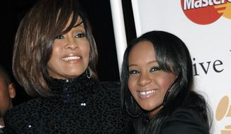 In this Feb. 12, 2011, file photo, singer Whitney Houston, left, and daughter Bobbi Kristina Brown arrive at an event in Beverly Hills, Calif. Singer Bobby Brown will receive a proclamation to build a domestic violence shelter in Atlanta in honor of his late daughter, Bobbi Kristina Brown. Bobbi Kristina died in hospice care July 26, 2015, about six months after she was found face-down and unresponsive in a bathtub in her suburban Atlanta townhome. Her former boyfriend, Nick Gordon was found responsible in a wrongful death lawsuit.  (AP Photo/Dan Steinberg, File)