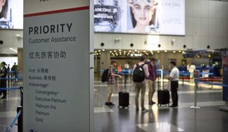 In this July 6, 2018, photo, travelers stand near a signboard at the American Airlines check-in counters at the Beijing Capital International Airport in Beijing. China is applauding U.S. airlines for bending to its demand that they cease referring to Taiwan as its own country on their websites, as American Airlines, Delta and United are among a wave of international carriers to remove references to Taiwan on their websites ahead of a Wednesday, July 25, 2018, deadline set by Chinese authorities. (AP Photo/Mark Schiefelbein)