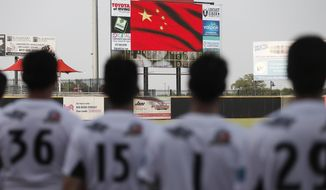 Texas AirHogs' Na Chuang (36), Song Yunqi (15), Yang Yanyong (1) and Yang Jin (29), all of China, stand for the playing of the Chinese national anthem before an American Association of Independent Professional Baseball game, Wednesday, July 18, 2018, in Grand Prairie, Texas. The small ballpark in Texas just a few miles from downtown Dallas is home this summer for the Chinese national baseball team under an unprecedented setup. The Chinese players are part of a revolving roster in a professional league, getting to play more games and against tougher competition to strengthen their team for future international competitions like the 2020 Olympics. (AP Photo/Brandon Wade)
