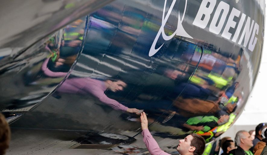 FILE- In this Feb. 5, 2018, file photo, Boeing worker Paul Covaci reaches out to touch a Boeing 737 MAX 7, the newest version of Boeing's fastest-selling airplane, during a debut for employees and media of the new jet in Renton, Wash. Boeing Co. says its second-quarter profit was $2.2 billion. The Chicago-based company said Wednesday, July 25, it had profit of $3.73 per share on revenue of $24.26 billion. Earnings, adjusted for non-recurring gains, were $3.33 per share. (AP Photo/Elaine Thompson, File)