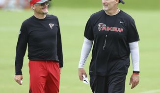 FILE - In this June 14, 2018, file photo, Atlanta Falcons general manager Thomas Dimitroff, left, and head coach Dan Quinn share a laugh during an NFL football minicamp in Flowery Branch, Ga. Falcons general manager Thomas Dimitroff and coach Dan Quinn, who have led the team to the playoffs the last two seasons, have signed three-year contract extensions. The deals were announced Wednesday, July 25, 2018, a day before players report for training camp. (Curtis Compton/Atlanta Journal-Constitution via AP, File)