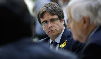 Former Catalan leader Carles Puigdemont, center, waits for the beginning of a news conference in Berlin, Germany, Wednesday, July 25, 2018. (AP Photo/Markus Schreiber)