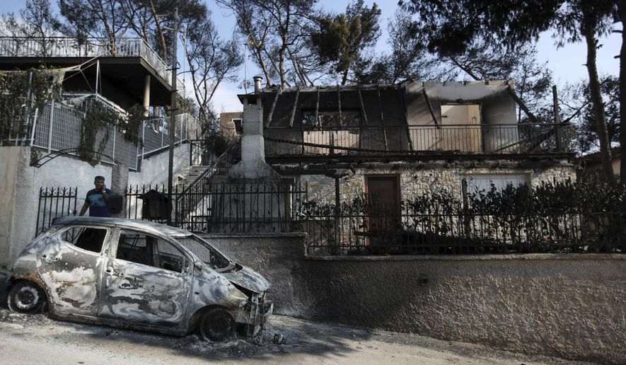 A man stands next to his burned house and car as he speaks ...