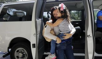 Immigrants from Brazil seeking asylum, Natalia Oliveira da Silva carries her daughter, Sara, 5, from a van as they arrive at a Catholic Charities facility, Monday, July 23, 2018, in San Antonio. Since their separation in late May, the girl had been at a shelter for immigrant minors in Chicago, while Oliveira was taken to various facilities across Texas. As the government faces a fast-approaching Thursday deadline to reunite hundreds of families, it is shifting the responsibility for their well-being to faith-based groups primarily in Texas and Arizona. (AP Photo/Eric Gay)