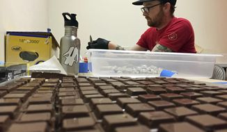 In this June 2, 2016 file photo, Chalice Farms production manager John Schuch wraps cannabis-infused hazelnut milk chocolates infused with marijuana in foil papers to prepare for sale at the company headquarters in Portland, Ore.  (AP Photos/Gillian Flaccus, File)