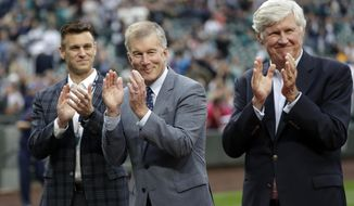 """FILE - In this May 18, 2018, file photo, Seattle Mariners general manager Jerry Dipoto, left, president Kevin Mather, center, and majority owner John Stanton applaud during a presentation before a baseball game against the Detroit Tigers in Seattle. In a statement Wednesday, July 25, 2018, the Mariners say they have """"made amends"""" with former female employees who made allegations of harassment against Mather. (AP Photo/Elaine Thompson, File)"""