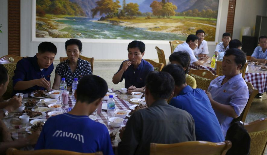 """People have their lunch at Pyongyang House of Sweet Meat, a restaurant specialized in dishes made of dog meat, in Pyongyang, North Korea, Wednesday, July 25, 2018. Euphemistically known as """"dangogi,"""" or sweet meat, dog has long been believed to be a stamina food in North and South Korea and is traditionally eaten during the hottest time of the year, giving a sad twist to old saying """"dog days of summer."""" (AP Photo/Dita Alangkara)"""