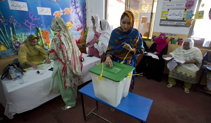 A Pakistani woman casts her vote at a polling station for the parliamentary elections in Islamabad, Pakistan, Wednesday, July 25, 2018. After an acrimonious campaign, polls opened in Pakistan on Wednesday to elect the country's third straight civilian election, a first for this majority Muslim nation that has been directly or indirectly ruled by its military for most of its 71-year history. (AP Photo/B.K. Bangash)