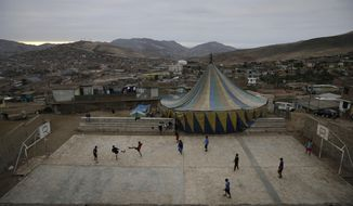 In this July 8, 2018, photo, youths play soccer next to the Tony Perejil circus tent set up in the shantytown of Puente Piedra on the outskirts of Lima, Peru. Urban expansion in the city of 10 million inhabitants makes it tough to find enough space to set up a tent in a centrally located neighborhood, while gangs of delinquents charge up to $10 a day for circuses to set up shop in depressed barrios. (AP Photo/Martin Mejia)
