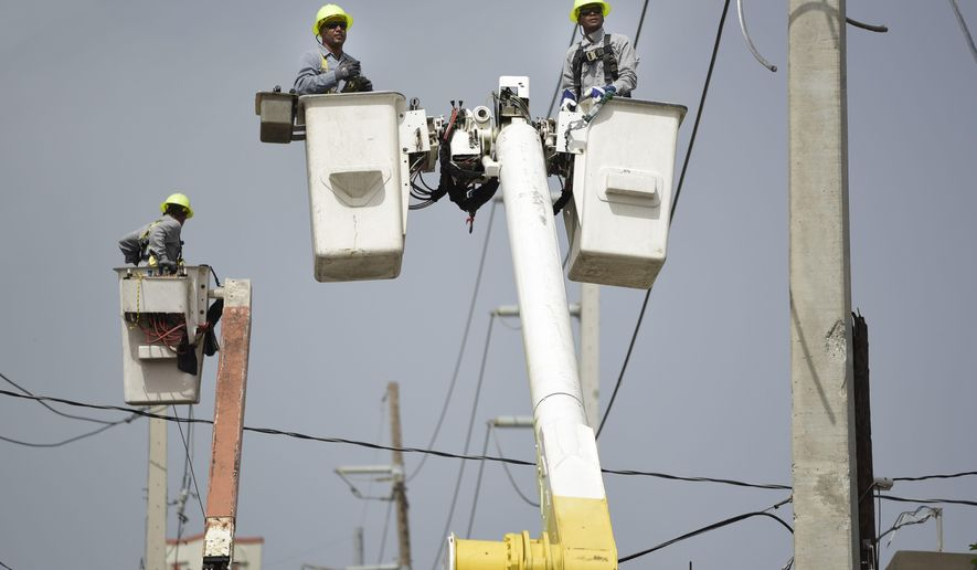 FILE - In this Oct. 19, 2017 file photo, Puerto Rico Electric Power Authority workers repair distribution lines damaged by Hurricane Maria in the Cantera community of San Juan, Puerto Rico. Federal lawmakers demand Wednesday, July 25, 2018 that Puerto Rico quickly privatize its bankrupt power company in a bid to end its turmoil and allow others to provide stable electricity in the aftermath of Hurricane Maria. (AP Photo/Carlos Giusti, File)