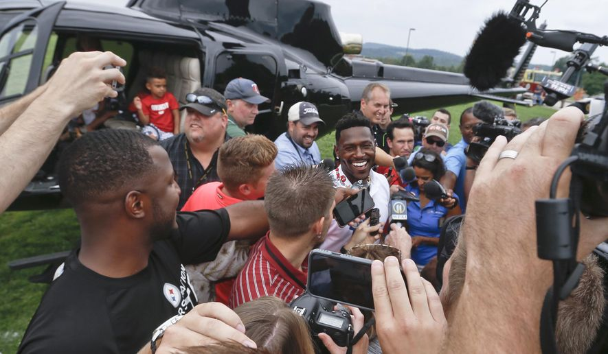 Pittsburgh Steelers wide receiver Antonio Brown, center, smiles as he talks with reporters after arriving for NFL football training camp with his family in a helicopter in Latrobe, Pa., Wednesday, July 25, 2018 . (AP Photo/Keith Srakocic)