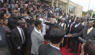 "Indian Prime Minister Narendra Modi, center in black suit, waves to Uganda Members of Parliament as Uganda President Yoweri Museveni, right, looks on in Uganda capital Kampala Wednesday July 25, 2018.  Modi is pledged to ""intensify and deepen"" the Asian country's engagement with Africa, saying Wednesday that ""Africa will be at the top of our priorities.(AP Photo / Stephen Wandera"