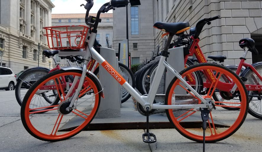 A Mobike dockless bikeshare bicycle is shown in this July 26, 2018, photo parked outside the Wilson Building in Washington, D.C. Mobike and rival company Ofo announced they were withdrawing their services from the District, blaming the city's regulatory restrictions. (Julia Airey/The Washington Times)