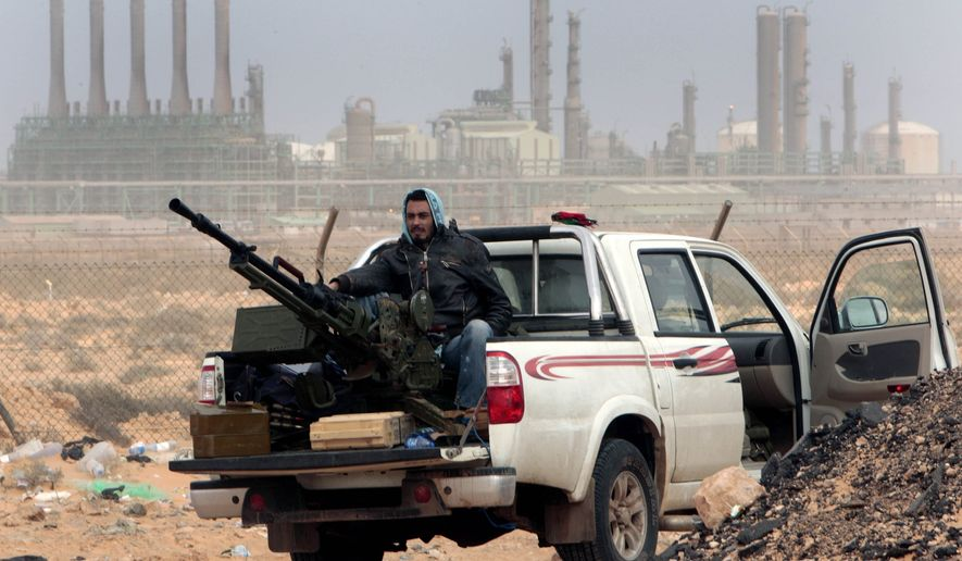 In this March 5, 2011, file photo, an anti-government rebel sits with an anti-aircraft weapon in front an oil refinery in Ras Lanouf, eastern Libya. The United States France, Germany, Italy, Spain and Britain have called upon forces loyal to a Libyan general to withdraw from three eastern oil terminals seized earlier this week, in a statement Monday, Sept. 13, 2016. The oil-rich North African country slid into chaos after the 2011 uprising that toppled and killed Moammar Gadhafi. (AP Photo/Hussein Malla, File)