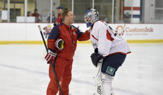 FILE - In this Sept. 18, 2015, file photo, Washington Capitals goaltending coach Mitch Korn, left, talks with Mark Dekanich, right, during media day at NHL hockey training camp in Arlington, Va. The New York Islanders have hired longtime goalie guru Mitch Korn as director of goaltending. Korn rejoins coach Barry Trotz. Korn was director of goaltending with Trotz and the Capitals last season when they won the Stanley Cup. (AP Photo/Nick Wass, File) **FILE**