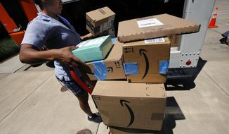 In this July 19, 2018, photo, a U.S. postal carrier delivers Amazon orders to an apartment complex in downtown Pittsburgh. Amazon's quarterly profit soared past $2 billion for the first time, as revenue from online shopping and its cloud computing business grew. (AP Photo/Gene J. Puskar)