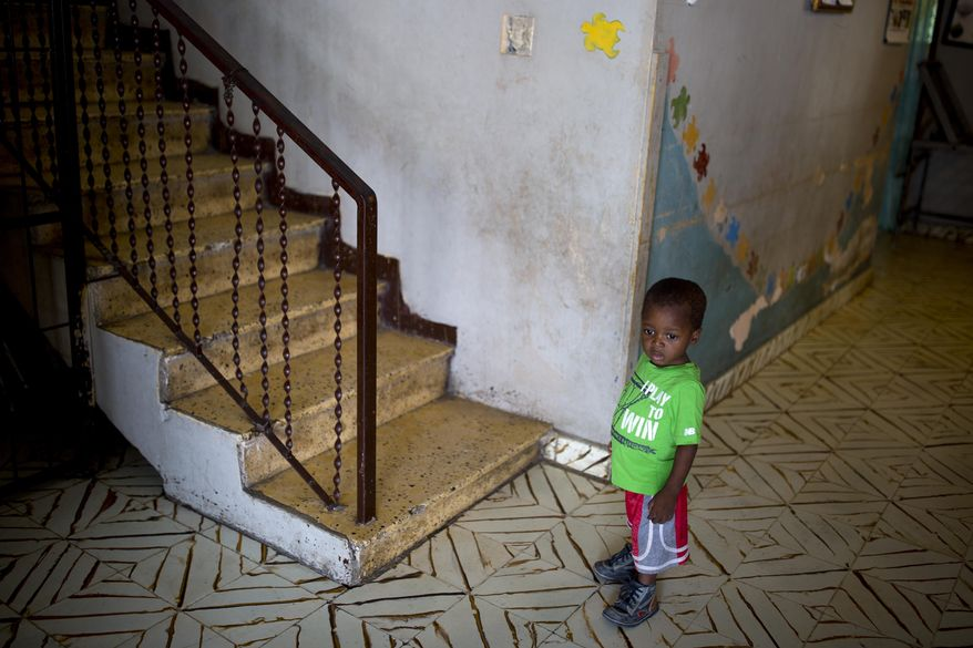 An orphan boy stands next to a staircase while looking out from the Nest of Hope orphanage in Port-au-Prince, Haiti on Thursday, June 28, 2018. A new program is cited by Haitian and foreign experts as evidence of the government's determination to modernize and strengthen an array of child-oriented policies and practices _ and lessen reliance on foreign-based charities and mission groups. (AP Photo/Dieu Nalio Chery)