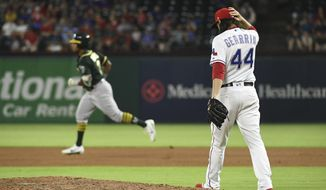 Texas Rangers relief pitcher Cory Gearrin walks back to the mound as Oakland Athletics' Khris Davis rounds the bases on a three-run home run during the seventh inning of a baseball game, Wednesday, July 25, 2018, in Arlington, Texas. (AP Photo/Jeffrey McWhorter)