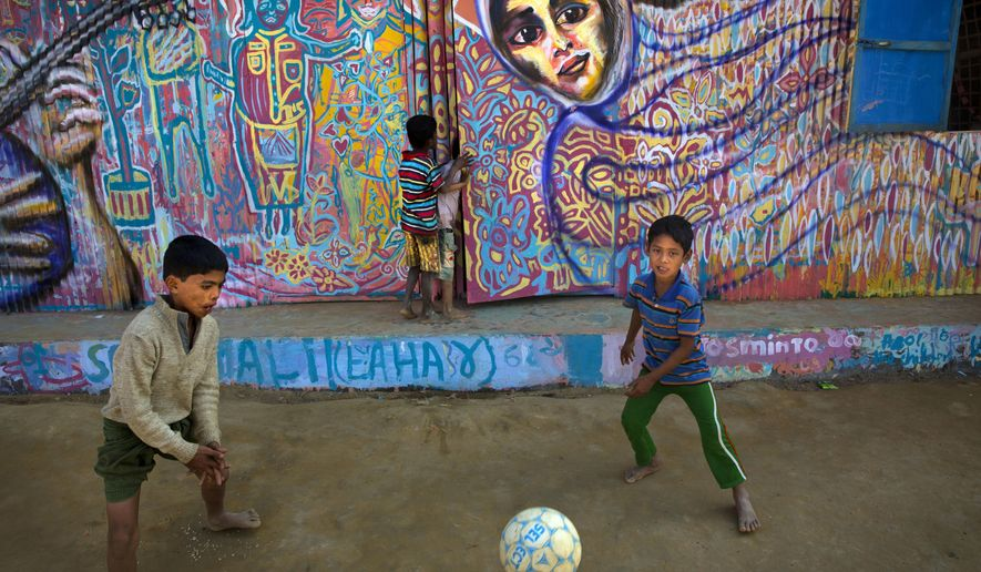 In this Sunday, Jan. 21, 2018, photo, Rohingya refugee children kick a soccer ball outside their makeshift school in the Kutupalong refugee camp near Cox's bazar, Bangladesh. The school walls are covered with mural created by public art organization called Artolution, who collaborate with refugees to create large pieces of art and use art as therapy in conflict zones around the world. (AP Photo/Manish Swarup)