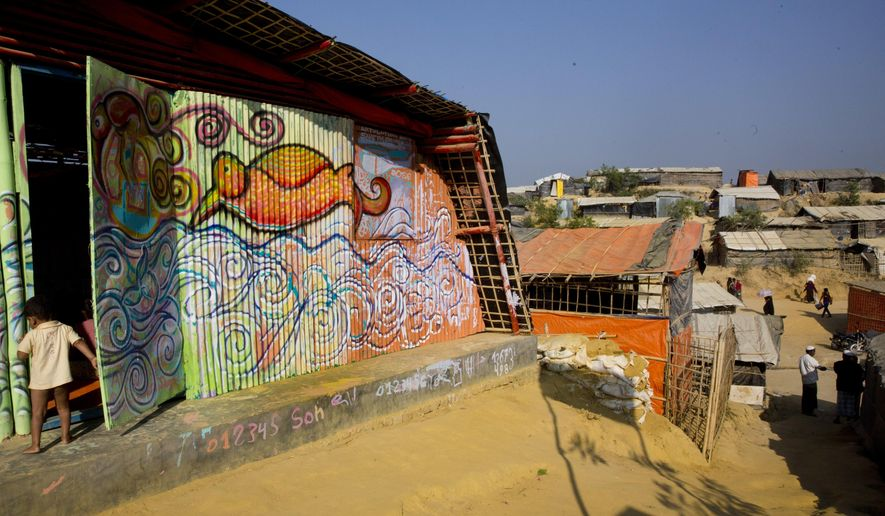 In this Jan. 21, 2018, photo, a life sizes mural is seen on the wall of a makeshift school for Rohingya refugee children at Kutupalong Refugee Camp near Cox's bazar, Bangladesh. The mural is created by a public art organization called Artolution, who collaborate with refugees to create large pieces of art and use art as therapy in conflict zones around the world. (AP Photo/Manish Swarup)