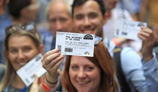 Fans brandish their tickets as they queue outside the Cavern Club in Liverpool, England, before an exclusive gig by former Beatles member Paul McCartney, Thursday July 26, 2018. The former Beatle will take to the stage at the famous venue on Mathew Street for a one-off exclusive gig. (Peter Byrne/PA via AP)