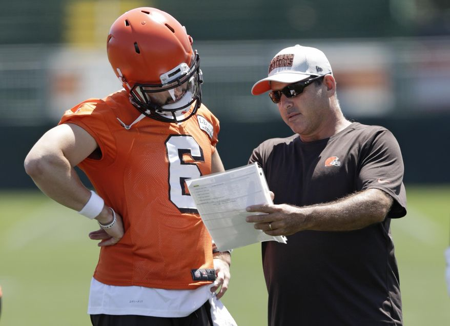 Cleveland Browns quarterbacks coach Ken Zampese, right, talks with quarterback Baker Mayfield at the NFL football team's training camp facility, Thursday, July 26, 2018, in Berea, Ohio. (AP Photo/Tony Dejak)