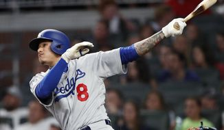 Los Angeles Dodgers' Manny Machado follows through on a solo home run in the sixth inning against Atlanta Braves in a baseball game Thursday, July 26, 2018 in Atlanta. (AP Photo/John Bazemore)