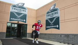 Philadelphia Eagles quarterback Carson Wentz (11) runs out of the facility during practice at NFL football training camp, Thursday, July 26, 2018, in Philadelphia. (AP Photo/Chris Szagola)