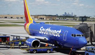 In this July 17, 2018, file photograph, ramp workers prepare a Southwest Airlines Boeing 737 for departure to Denver from Minneapolis International Airport in Minneapolis. (AP Photo/David Zalubowski) ** FILE **