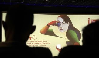 Journalists are silhouetted against the logo presenting the 75th edition of the festival, during its presentation in Rome, Wednesday, July 25, 2018. The Venice Film Festival will run from Aug. 29 through Sept. 8, 2018, at the Venice Lido. (AP Photo/Gregorio Borgia)