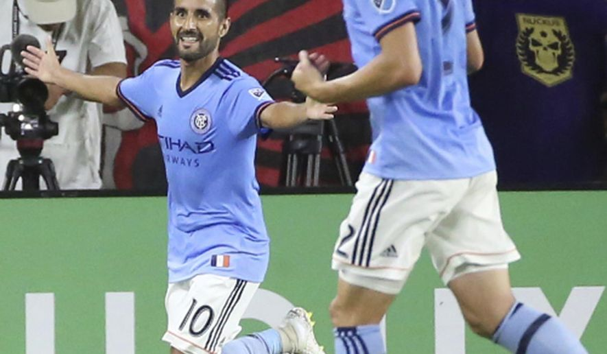 New York City FC's Maximiliano Moralez (10) and Ben Sweat (2) celebrate after a Moralez goal against Orlando City during an MLS soccer match Thursday, July 26, 2018, in Orlando, Fla. (Stephen M. Dowell/Orlando Sentinel via AP)