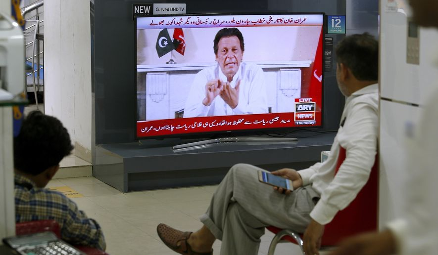 """People listen the speech of Pakistani politician Imran Khan, chief of Pakistan Tehreek-e-Insaf party, telecasting on news channels at a shop in Islamabad, Pakistan, Thursday, July 26, 2018. Khan declared victory Thursday for his party in the country's general elections, promising a """"new"""" Pakistan following a vote that was marred by allegations of fraud and militant violence. (AP Photo/Anjum Naveed)"""