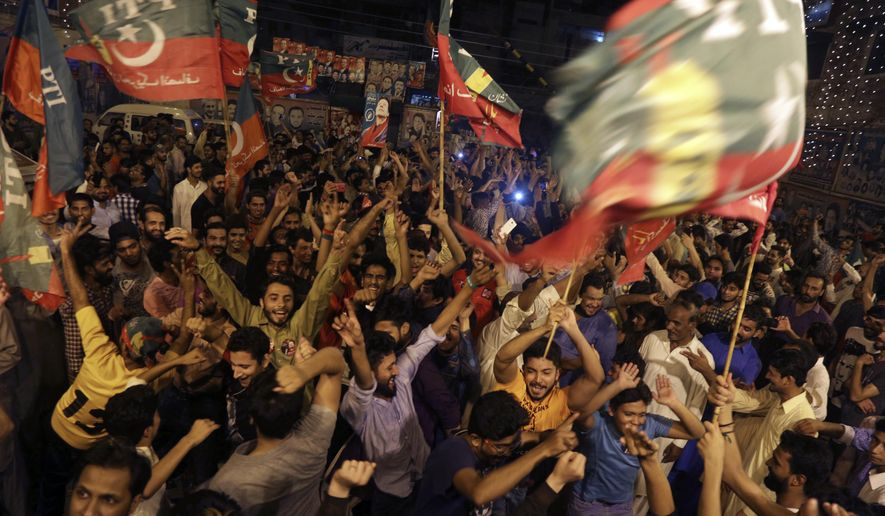 Supporters of Pakistani politician Imran Khan, chief of Pakistan Tehreek-e-Insaf party, celebrate projected unofficial results announced by television channels indicating their candidates' success in the parliamentary elections in Islamabad, Pakistan, Wednesday, July 25, 2018. (AP Photo/K.M. Chaudary)