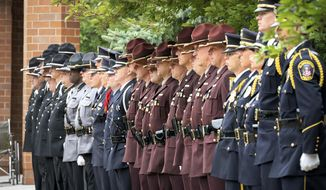 An honor guard of officers from around the region stand at the entrance to North Heights Lutheran Church as the body of Correctional Officer Joseph Gomm arrives in a casket draped with a U.S. flag, Thursday, July 26, 2018 in Arden Hillis, Minn. The 45-year-old corrections officer was killed by an inmate at the Stillwater prison last week. Gomm is the first prison guard killed in the line of duty in Minnesota. (Glenn Stubbe/Star Tribune via AP)