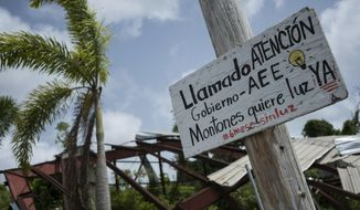 "In this July 20 photo, a sign in Spanish that reads ""Attention government, AEE. Montones wants light. Six months without light,"" hangs from a pole in Las Piedras, Puerto Rico. A scattering of hardware stores, barbershops and corner stores across the island are embracing solar energy, trying to wean themselves off a state-owned power company that remains heavily dependent on petroleum. (AP Photo/ Dennis M. Rivera Pichardo)"