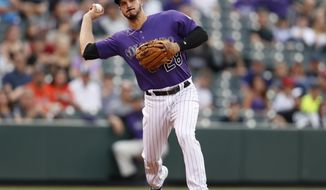 In this Wednesday, July 25, 2018, photo, Colorado Rockies third baseman Nolan Arenado throws to first base for a put out against the Houston Astros in the first inning of a baseball game in Denver. The Rockies All-Star received a brief taste of success last season when the team made it to the postseason as an NL wild-card. (AP Photo/David Zalubowski)