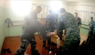 In this video grab provided by the Russian independent newspaper Novaya Gazeta on Wednesday, July 26, 2018, a prisoner is beaten while handcuffed at the prison in Yaroslavl, Russia, about 270 kilometers (169 miles) north-east of Moscow. The video caused wide concern after the newspaper published it last week. Irina Biryukova, a lawyer who refused to reveal her location because of security concerns, obtained the video and says she doesn't intend to return to Russia until she is sure that all those involved have been arrested. (Novaya Gazeta via AP)