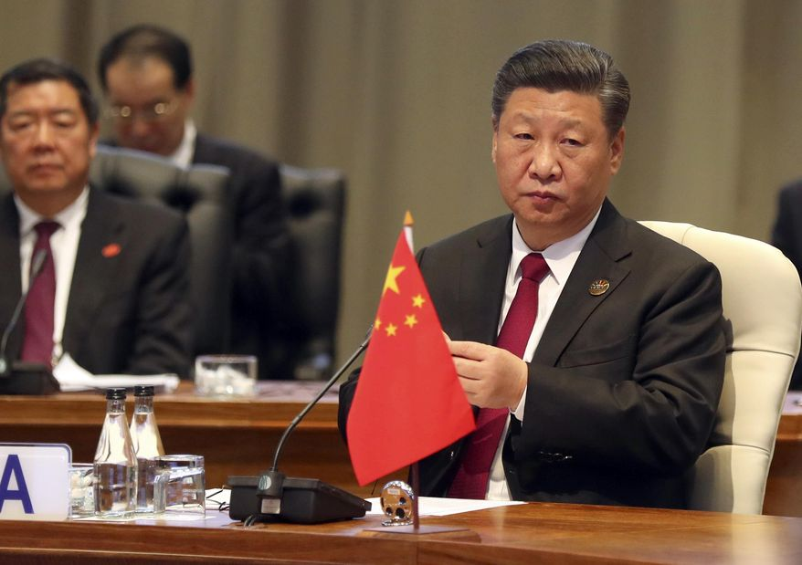 China's President Xi Jinping takes his seat for the first closed session of the BRICS summit, in Johannesburg, South Africa, Thursday, July 26, 2018. The five leaders of the BRICS emerging economies have gathered in South Africa for an annual summit where the United States is being criticized for escalating tariffs on foreign goods. (Mike Hutchings/Pool Photo via AP) ** FILE **