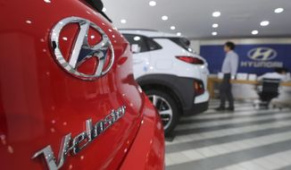 The logo of Hyundai Motor Co. is seen on a car displayed at its showroom in Seoul, South Korea, Thursday, July 26, 2018. Hyundai Motor Co. says its net profit for the second quarter has fallen 14 percent over a year earlier due to the South Korean won's strength against the U.S. dollar. (AP Photo/Ahn Young-joon)