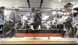 A scale model of the Russian warship Dmitrii Donskoi is surrounded by the media before a news conference in Seoul, South Korea, Thursday, July 26, 2018. A South Korean company is backing off its claim to have found the sunken Russian warship with an enormous cargo of gold. (AP Photo/Lee Jin-man)