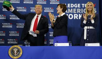 "Ivanka Trump, right, and Gov. Kim Reynolds, R-Iowa, center, look on as President Donald Trump holds up a ""Make Our Farmers Great Again"" hat during a roundtable discussion on workforce development at Northeast Iowa Community College, Thursday, July 26, 2018, in Peosta, Iowa. (AP Photo/Evan Vucci)"