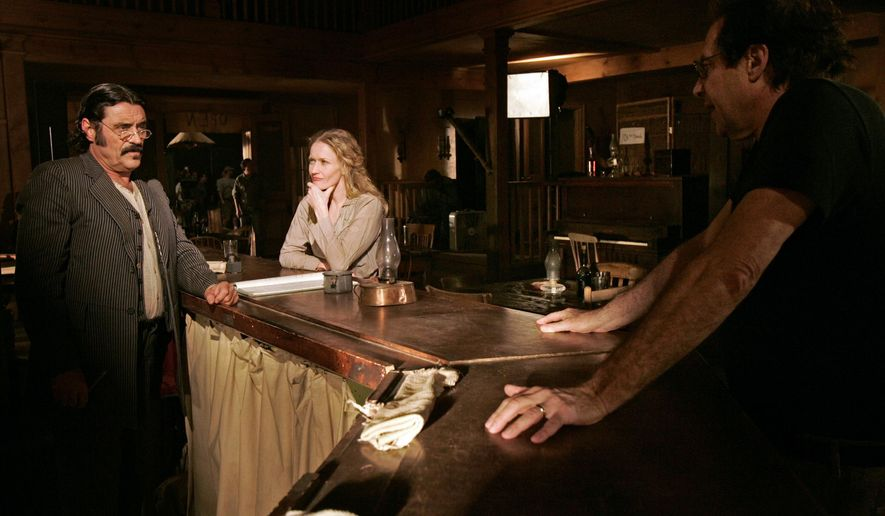 """FILE - This Feb. 9, 2005 file photo shows actors Ian McShane, who portrays Al Swearengen, left, and Paula Malcomson, who portrays Trixie, center, on the set with David Milch, creator of the HBO series """"Deadwood,"""" in Santa Clarita, Calif. HBO says it's greenlighted a long-discussed movie based on the Western drama that ended a dozen years ago. The critically acclaimed, award-winning  series was set in the rough-and-tumble South Dakota mining town of the title. (AP Photo/Kevork Djansezian, File)"""