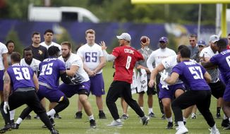 Minnesota Vikings quarterback Kirk Cousins, center, works among rookie prospects as they reported to the NFL football team complex for the opening of training camp Wednesday, July 25, 2018, in Eagan, Minn. (AP Photo/Jim Mone)