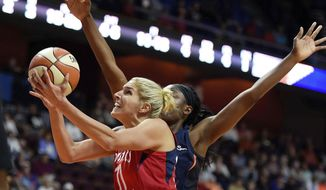 In this June 13, 2018, file photo, Washington Mystics forward Elena Delle Donne (11) shoots past Connecticut Sun forward Chiney Ogwumike during the first half of a WNBA basketball game in Uncasville, Conn. (Sean D. Elliot/The Day via AP) **FILE **