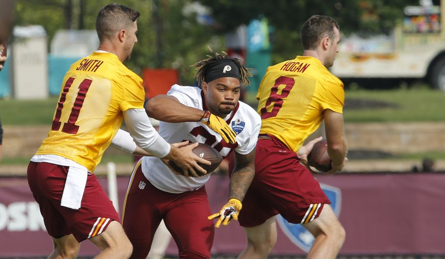 Washington Redskins quarterback Alex Smith (11) hands the ball off to running back Derrius Guice (29) during the morning session of the Redskins NFL football training camp in Richmond, Va., Friday, July 27, 2018. (AP Photo/Steve Helber) ** FILE **
