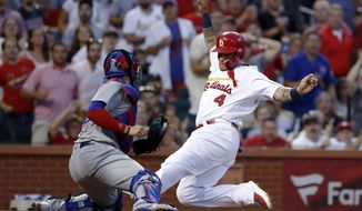 St. Louis Cardinals' Yadier Molina (4) scores past Chicago Cubs catcher Victor Caratini during the third inning of a baseball game Friday, July 27, 2018, in St. Louis. (AP Photo/Jeff Roberson)