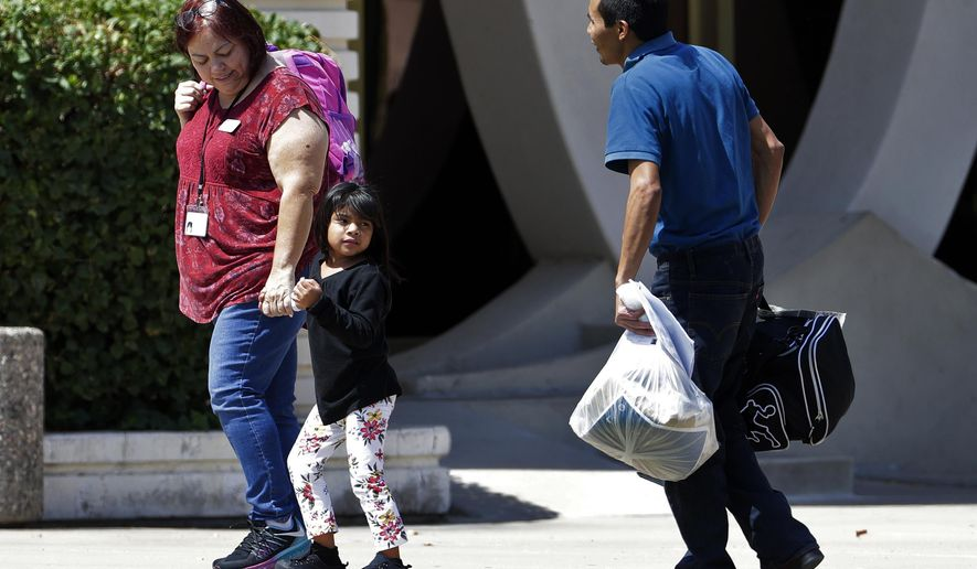 A child holds the hand of a Lutheran Social Services worker as she looks back to a man as they arrive at Lutheran Social Services, Thursday, July 26, 2018 in Phoenix. Lutheran Social Services stated they were expecting reunited families separated at the border when apprehended entering the United States to come through their facility. (AP Photo/Matt York)