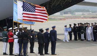 A U.N. honor guard carries a casket containing remains believed to be from American servicemen killed during the 1950-53 Korean War after arriving from North Korea, at Osan Air Base in Pyeongtaek, South Korea, Friday, July 27, 2018. The U.N. Command says the 55 cases of war remains retrieved from North Korea will be honored at a ceremony next Wednesday at a base in South Korea. (AP Photo/Ahn Young-joon, Pool)